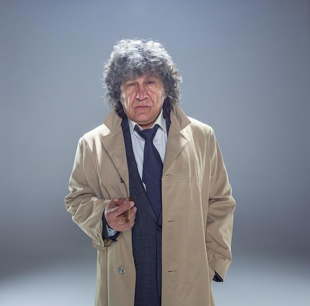 L'uomo senior con il sigaro come agente investigativo o capo della mafia sullo spazio grigio dello studio Foto Gratuite