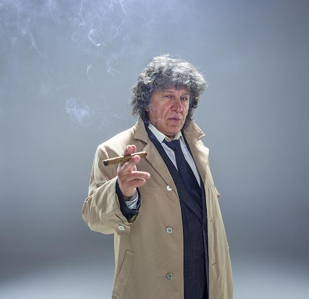 L'uomo anziano con sigaro come detective o capo della mafia su grigio Foto Gratuite