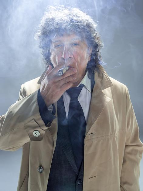 L'uomo anziano con sigaro come detective o capo della mafia Foto Gratuite