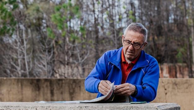 公園で新聞を読んでメガネの年配の男性 Premium写真
