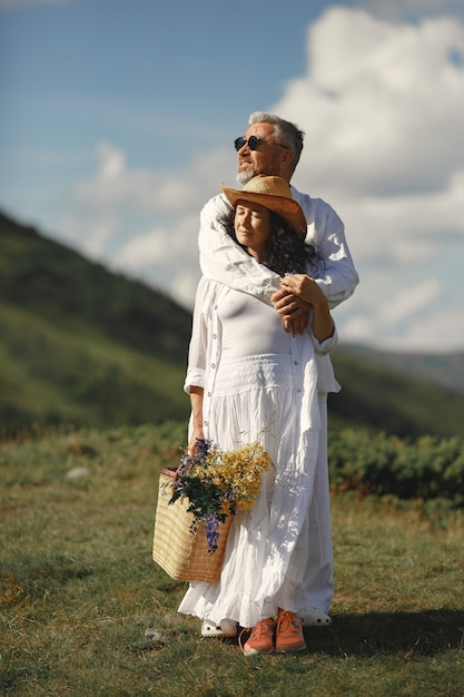 Senior man and woman in the mountains. woman with basket of flowers. man in a white shirt. Free Photo