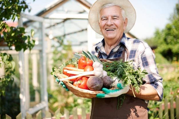 野菜のたんすで畑で働く年配の男性 無料写真