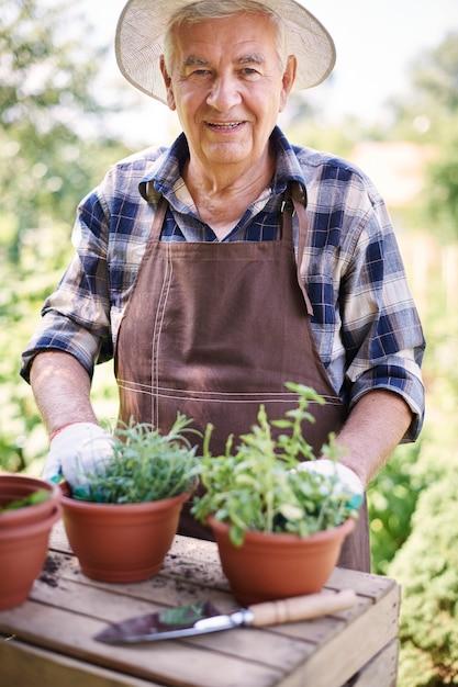 花とフィールドで働く年配の男性 無料写真