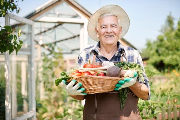 野菜と一緒に畑で働く年配の男性 無料写真