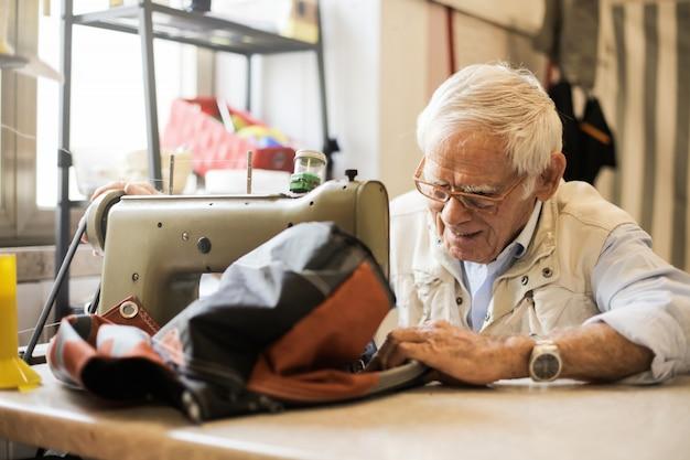 Senior man working with a sewing machine Premium Photo