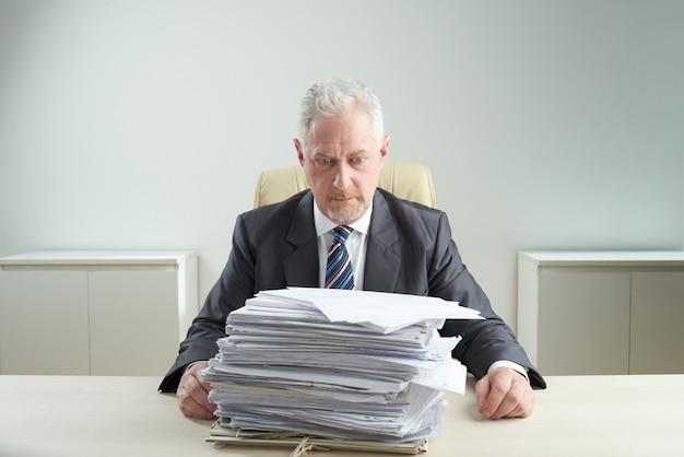 Senior manager overwhelmed by work Free Photo
