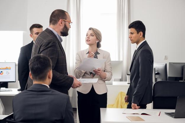 上級管理職とインターンは人事会社のホワイトオフィスで会議を開きます。オープンゾーン。数人 Premium写真