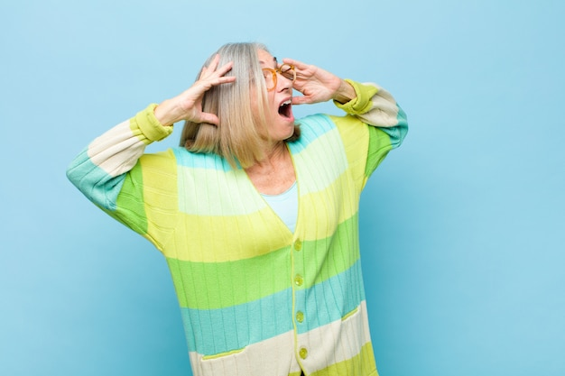 Senior or middle age pretty woman with open mouth, looking horrified and shocked because of a terrible mistake, raising hands to head Premium Photo