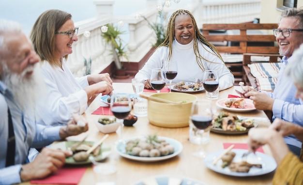 パティオで夕食を楽しんでいる高齢の多民族の人々 Premium写真