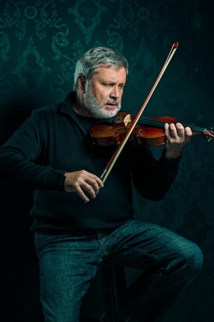 Старший музыкант играет на скрипке с палочкой на черном Бесплатные Фотографии