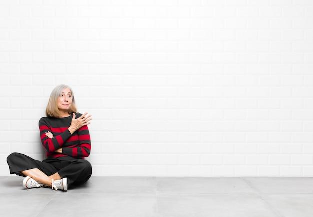 疑わしい説明や考えについて疑問に思って、混乱して無知な感じのシニアまたは中年のきれいな女性 Premium写真