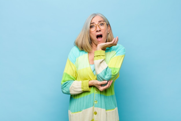 シニアの女性または中年のプリティウーマンはショックと信じられない思いで口を開いて、頬に手を当て、腕を組んで、驚いて、驚いた Premium写真