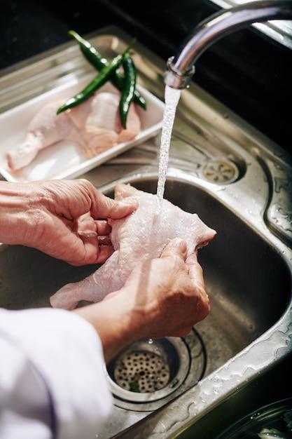 Senior person rinsing chicken thights Premium Photo