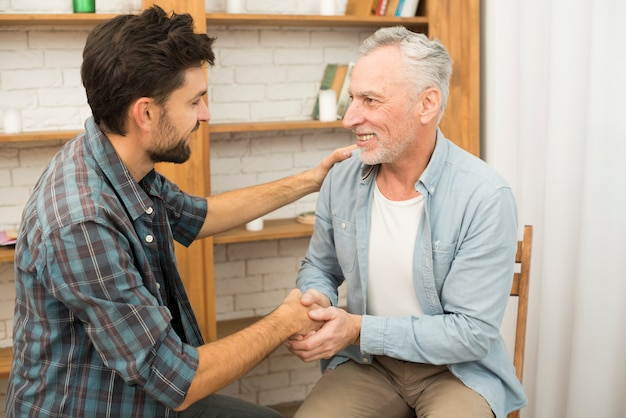Senior positive man shaking hands with young happy guy in room Free Photo