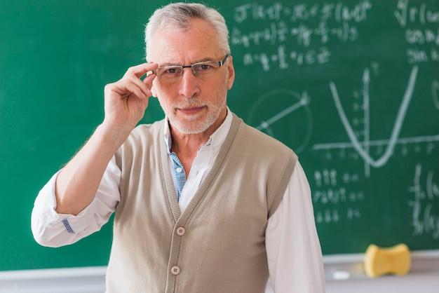 Senior professor correcting glasses against chalkboard with math problem Free Photo