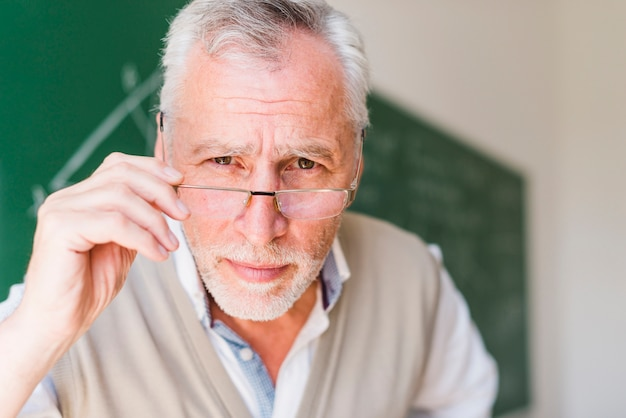 Senior professor putting on glasses in classroom Free Photo