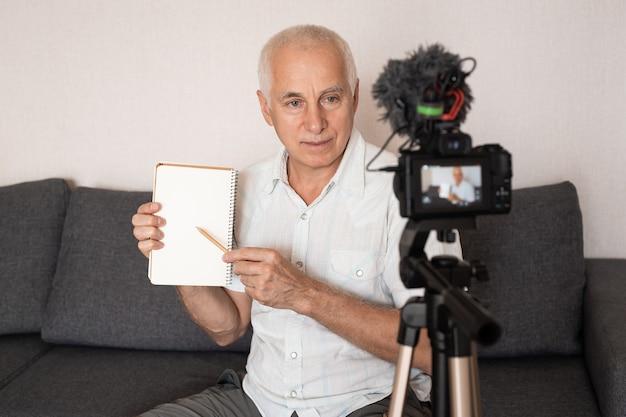 Старший профессор показывает что-то в блокноте, делая видео для лекции дома Premium Фотографии