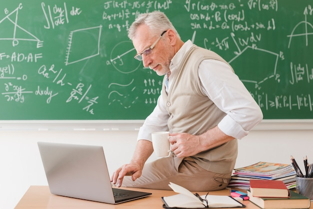 Senior professor sitting on desk and typing on laptop Free Photo