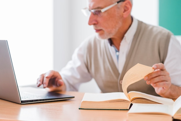 Senior professor working with laptop while holding page of book Free Photo