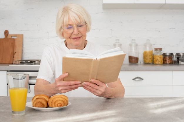 Senior reading a book in the kitchen Free Photo