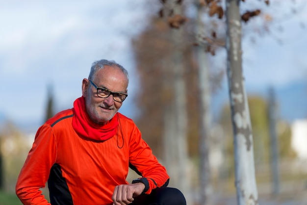 Senior runner man resting at the park while monitoring his exercise Premium Photo