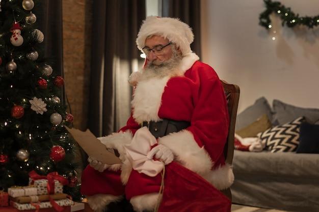 Senior santa reading a christmas letter Free Photo
