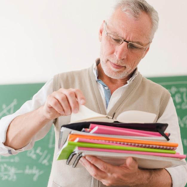 Senior teacher checking notepads in classroom Free Photo