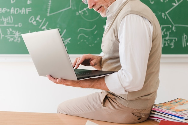 Senior teacher sitting on desk and surfing on laptop Free Photo