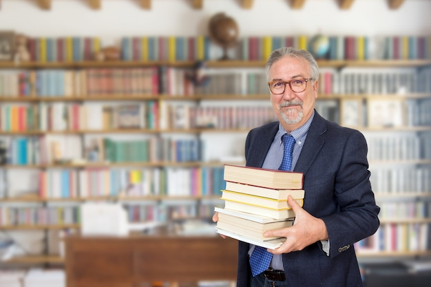 Senior teacher standing holding a book in front of a bookcase Premium Photo