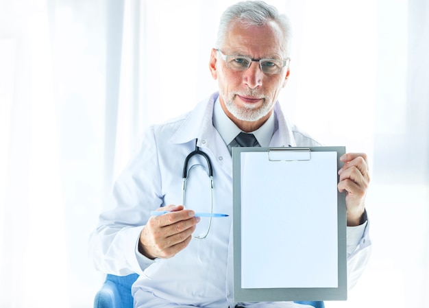 Senior therapist showing blank clipboard Free Photo