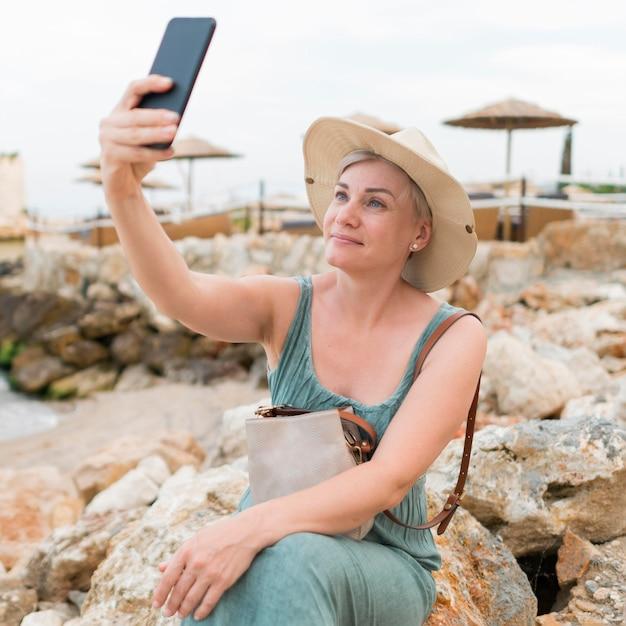 Selfieを取ってシニア観光女性 無料写真