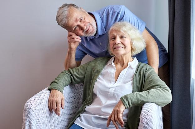 Старшая жена и муж позирует, улыбаясь на уютном диване у себя дома, женщина сидит, пока ее муж стоит за ней. портрет Premium Фотографии