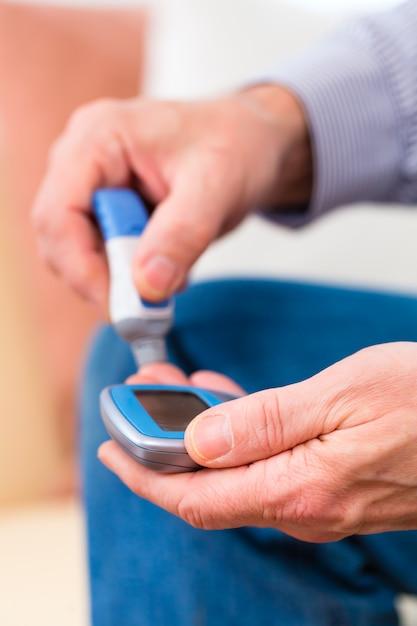 Senior with diabetes using blood glucose analyser Premium Photo