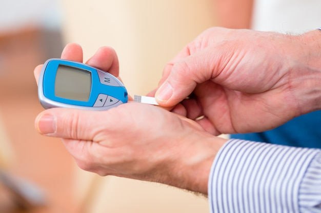 Senior with diabetes using blood glucose analyser Premium Photo