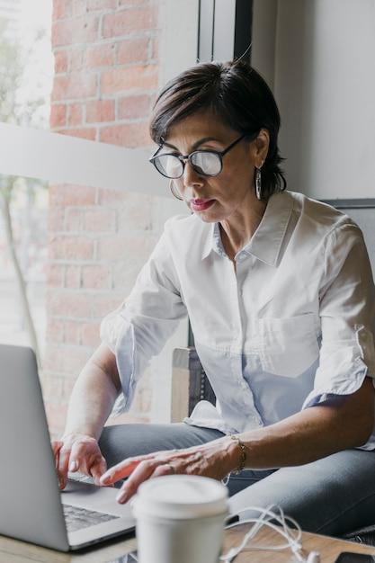 Senior with eyeglasses working on laptop Free Photo