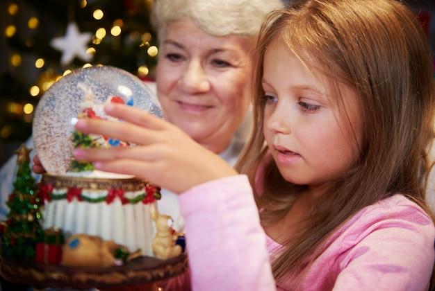 Anziano con la ragazza che guarda il globo della neve di natale Foto Gratuite