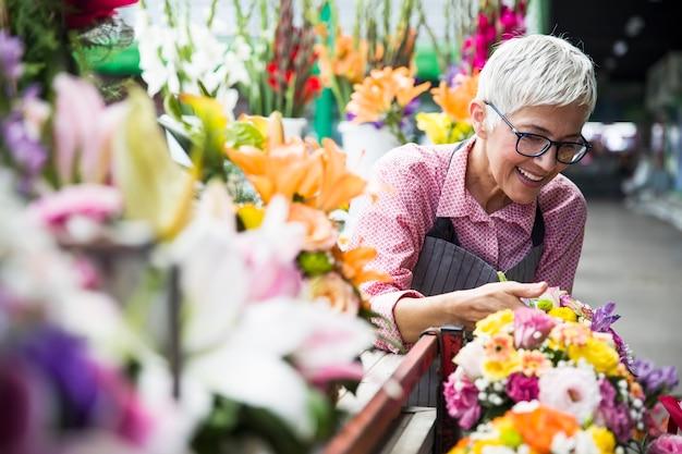 Senior woman arranges flowers on local flower market Premium Photo