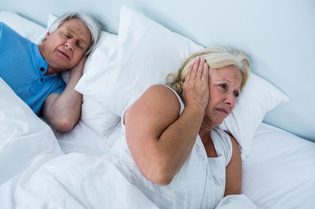 Senior woman blocking ears while man snoring Premium Photo
