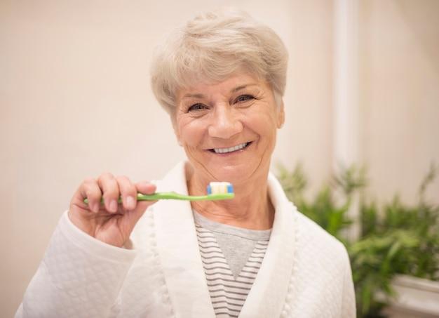 Donna maggiore che pulisce i suoi denti Foto Gratuite