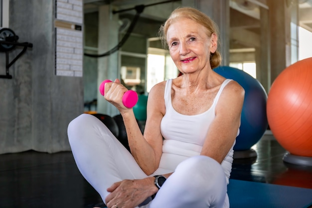 Senior woman caucasian training arm with dumbell at fitness gym. Premium Photo