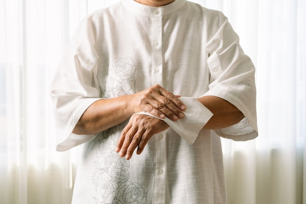 Senior woman cleaning her hands with white soft tissue paper. isolated on a white backgrounds Premium Photo