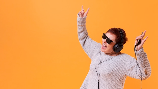 Senior woman dancing and listening music with copy space Free Photo