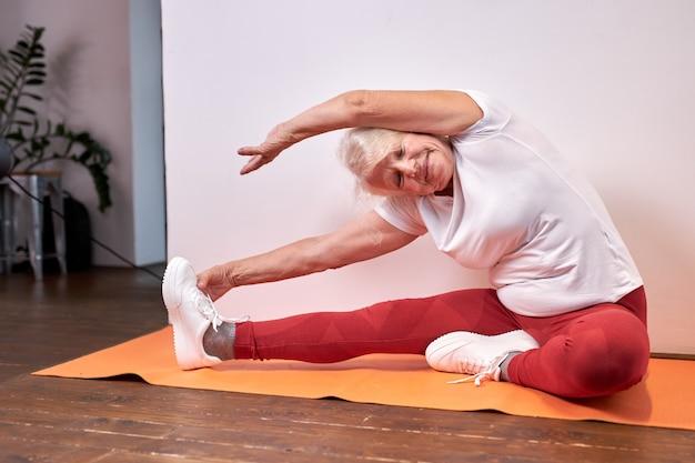 年配の女性は床で自宅でスポーツ運動をし、腕と脚を伸ばして美しい健康な女性、ヨガを楽しんで、健康的なライフスタイルをリードします Premium写真