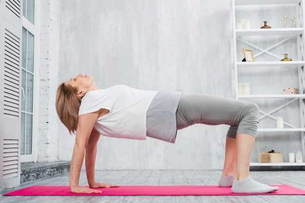 Senior woman doing stretching exercise over pink mat at home Free Photo