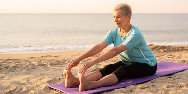 Senior woman doing yoga on the beach Free Photo