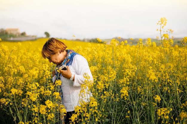 Senior woman in a field of yellow flowers Premium Photo