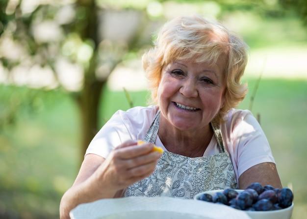 Старший женщина, имеющая абрикос в саду Premium Фотографии