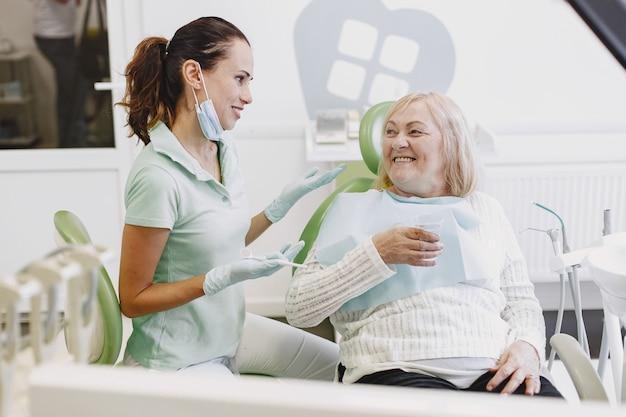 Старшая женщина, имеющая стоматологическое лечение в кабинете стоматолога. женщина лечится от зубов Бесплатные Фотографии