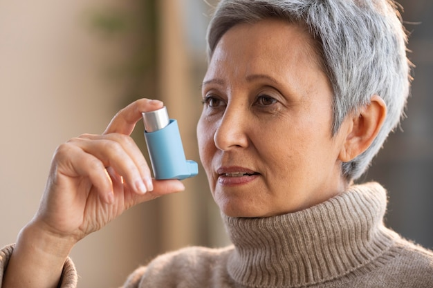 Senior woman holding asthma inhaler Free Photo