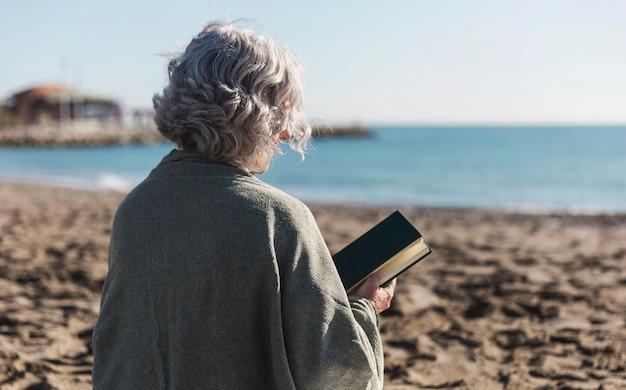 Старшая женщина держа взгляд задней части книги Бесплатные Фотографии